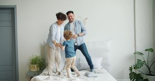 Mother father and son jumping dancing on bed in bedroom at home together stock footage
