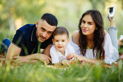 Mother, father and son lying on the grass in park on picnic. Stock Image