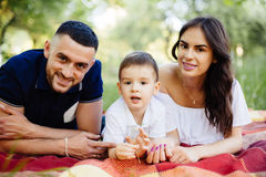 Mother, father and son lying on the grass in park on picnic. Royalty Free Stock Images