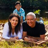 Outdoor family portrait. Mother, Father and son outdoor lifestyle portrait in a park setting Royalty Free Stock Photo