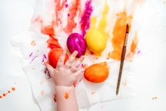 Mother, father and son are painting eggs. Happy family are preparing for Easter. Coloring eggs for Easter with colorful bright colors, the hands of a baby, a royalty free stock photo