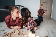 Mom kisses dad on the floor in the nursery. A mother, father and son are playing together on the floor stock photos