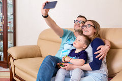 Mother, father and son smile, do selfie on the phone sitting on stock photo