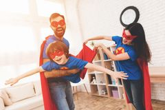 Mother, father and son in suits of superheroes. Incredibles in a bright room. stock photography
