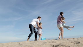 Mother and Father Spinning Their Son and Daughter on the Beach stock video