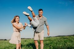 Mother and father swinging son in sunnny summer day. Outdoor royalty free stock photography