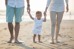 Mother and father is teaching her daughter walks on the beach stock photos