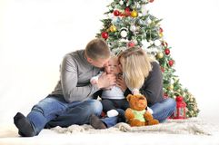 Mother, the father and their small child sits near Christmas tree Royalty Free Stock Photography