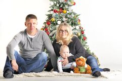 Mother, the father and their small child sits near Christmas tree Royalty Free Stock Photo