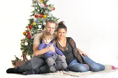 Mother, the father and their small child sits near Christmas tree Stock Image