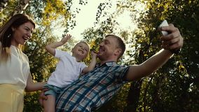 Mother, father and their son taking picture together in nature. Sun rays shine through tree leaves. Slow motion stock video footage