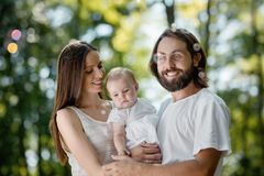 Mother, father and there little baby girl dressed in the white casual clothes are in the park and looking at the soap royalty free stock photography