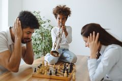 Mother and father trying to play chess while their child plays trumpet Stock Image