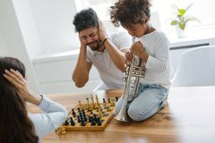 Mother and father trying to play chess while their child plays trumpet Royalty Free Stock Photography