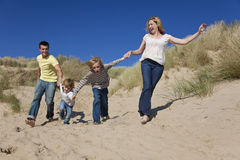Mother, Father and Two Boys Family Fun At Beach. A happy family of mother, father and two sons, running holding hands and having fun in the sand dunes of a sunny Royalty Free Stock Photos