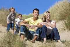 Mother, Father & Two Boys Family Sitting At Beach. A happy family of mother, father and two sons, sitting and having fun in the sand dunes of a sunny beach Royalty Free Stock Image