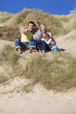 Mother, Father & Two Boys Family Sitting At Beach. A happy family of mother, father and two sons, sitting and having fun in the sand dunes of a sunny beach Stock Images