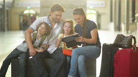 Mother and father with two children are sitting in the waiting room of the railway station or an airport. Beautiful Mother and Handsome Father with Two Children stock footage