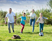 Mother and father with two kids  running after  ball Stock Photos