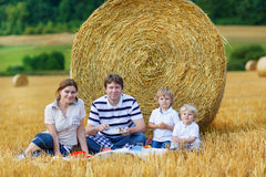 Mother, father and two little sons picnicking together Stock Photo