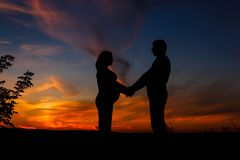Mother and father waiting for a baby on a sky background. Happy family stock photo