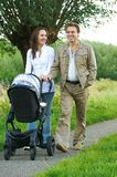 Mother and father walking outdoors with baby stroller Royalty Free Stock Images
