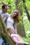 Mother and father watching daughter relax on tree trunk in forest Royalty Free Stock Image
