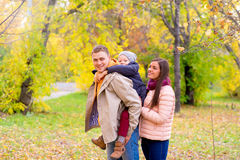 Mother and Father With Young Son On his back Autumn Park. Walks between trees, smiling together Stock Images