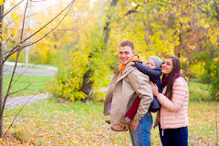 Mother and Father With Young Son On his back Autumn Park. Walks between trees, smiling together Royalty Free Stock Photo