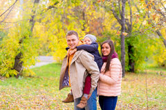 Mother and Father With Young Son On his back Autumn Park. Walks between trees, smiling together Stock Photos