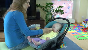 Mother feed baby girl in car seat. Vegetable porridge. stock video