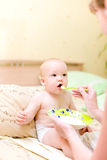 Mother feed baby by porridge Royalty Free Stock Photography