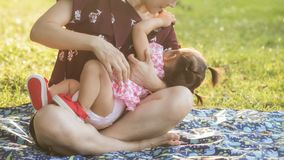 Mother feed breastmilk to her daughter in park. Mom feeds 11 months old baby girl breastfeeding in park with foliage sunset bokeh background in summer stock images