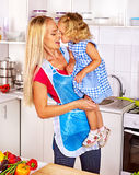 Mother  feed child at kitchen. Royalty Free Stock Image