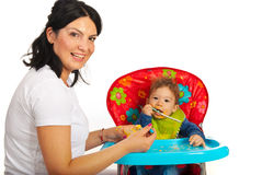 Mother feed her baby boy. Happy mom feeding her baby boy with vegetables puree Royalty Free Stock Photos