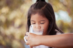 Mother feed a milk from glass to daughter Stock Images