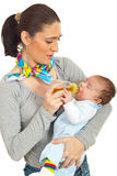Mother feed newborn baby. Mid adult mother feed her newborn baby boy with tea for cramps isolated on white background Royalty Free Stock Photos