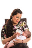 Mother feed newborn baby. Mother sitting on chair and feeding newborn baby isolated on white background Royalty Free Stock Image