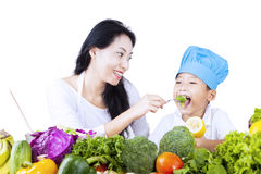 Mother feed young chef Stock Images