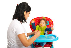 Mother feedin baby with puree Stock Images