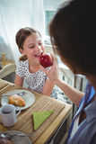 Mother feeding apple to her daughter while having breakfast Royalty Free Stock Images