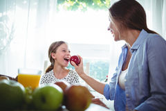 Mother feeding apple to her daughter while having breakfast Stock Photos