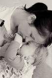 Mother feeding baby. Closeup of a loving mother, feeding a baby girl with a bottle.  Black and white Stock Images