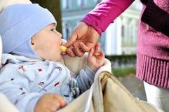 Mother feeding baby. Corn ball Royalty Free Stock Photography
