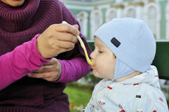 Mother feeding baby. With spoon Stock Photos