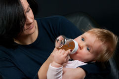 Mother feeding baby with bottle Stock Images