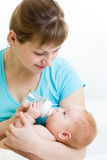 Mother feeding baby from bottle Stock Images