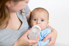 Mother feeding baby from bottle. Mother feeding her cute baby from bottle Stock Images