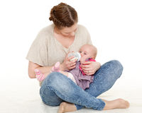Mother feeding baby from bottle. Young mother feeding baby from bottle on a white background. Happy family Royalty Free Stock Images