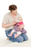Mother feeding baby from bottle. Young mother feeding baby from bottle on a white background. Happy family Stock Photos